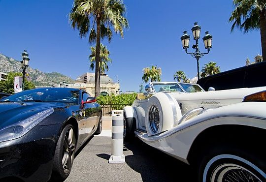 The Investing Style of William O'Neil - The Life of William O'Neil; Picture of a wealthy stock investor with two luxury cars, one black sports car and one while older style Roll Royce car.
