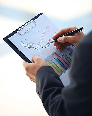 Value Investing - The Value Investor; picture of man holding clipboard with graph checking revenue data for trends to bottom out for good value to buy now