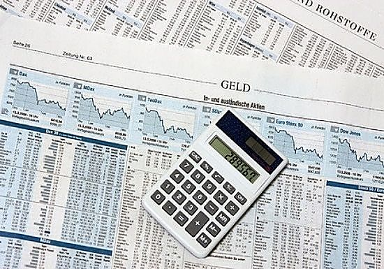 Value Investing - Finding Good Value Stocks; picture of financial newspaper showing stock price data and index charts with a calculator sitting on top of the paper