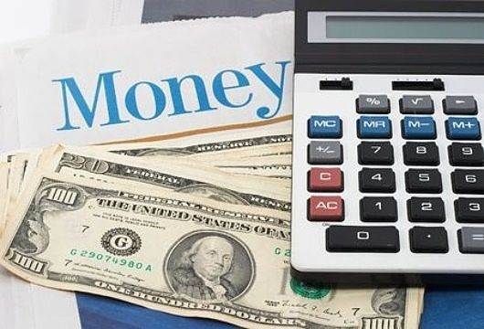 Profits and the Economy - Tracking the Economy; picture of the United States of America one hundred dollar bills with a financial calculator on top with writing tracking the money