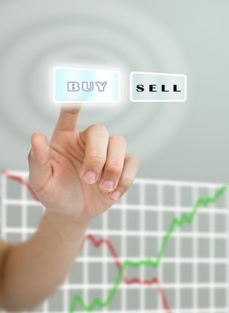 Position Trading - picture of a position trader using their hand to point at a buy button instead of the sell button with a stock chart on a glass background screen