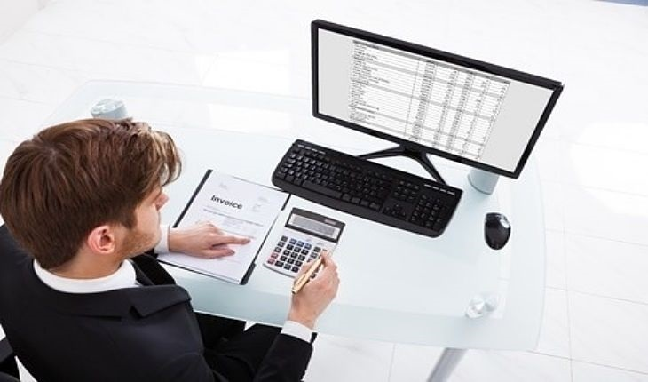 Speculative Investing Strategies - Value Trading; picture of a trader using a calculator to work out the trade to take while sitting in front of a computer screen