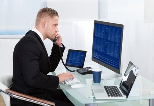 Speculative Investing Strategies - Value Trading with Short Options; picture of a stock investor on a phone to a broker to place a trade while looking at charts on a computer screen