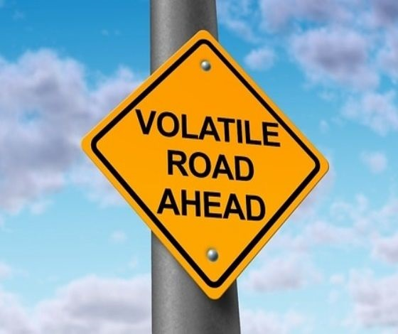 Risk Analysis - Why Stock Prices Fluctuate; picture of a road sign with a yellow background saying volatile road ahead for stocks in black writing