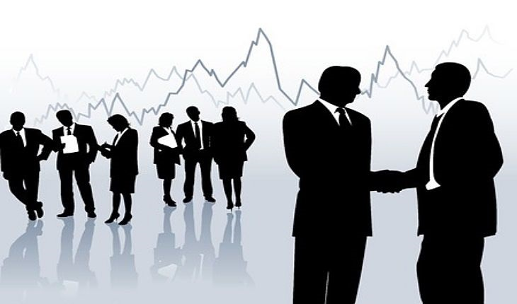 Stock Market Theories - Wyckoff Market Analysis; picture of an investors conference standing around talking and watching the stock market chart on a glass display panel